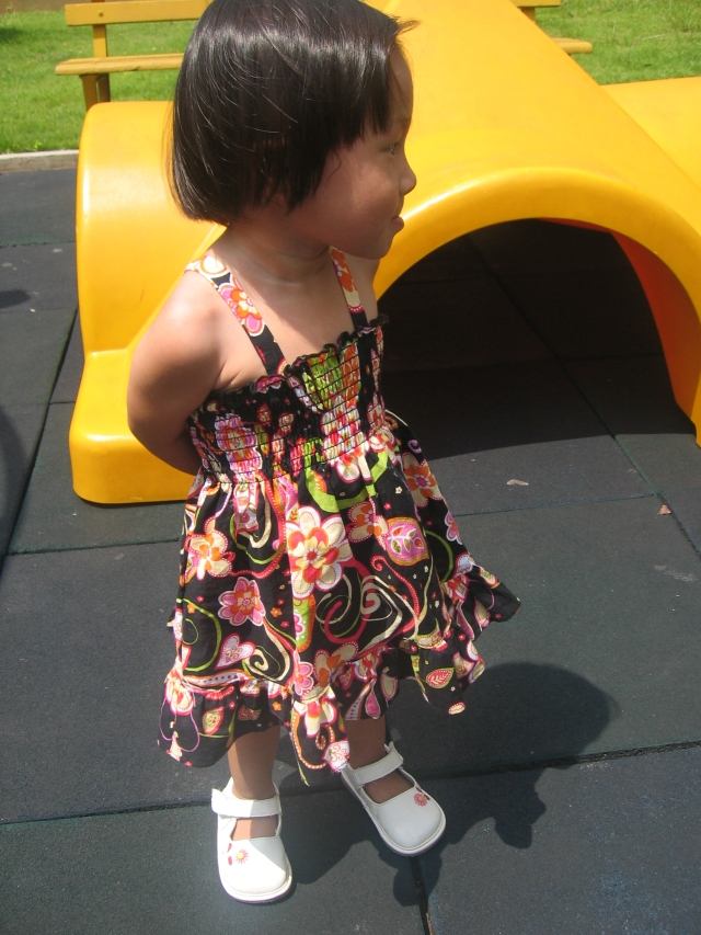 While I met with the foster family, Koen and Li Li attempted to play on the playground, but it was too hot.  Li Li often stands with her hands behind her back like this.