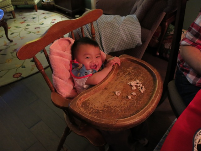 Sitting in the same highchair his daddy did - but needing a towel to help him fit better.